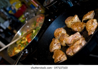 Two separate frying pans containing meat and vegetables.