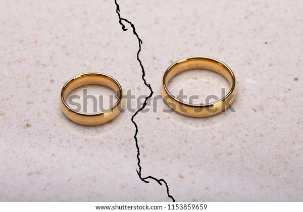 Zwei getrennte Hochzeitsringe auf gerissener Oberfläche