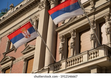 Two Serbian flags flown off a balcony of an old building, one with the coat of arms and one without it