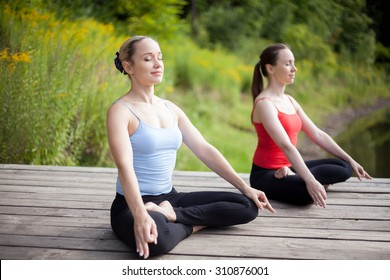 Two serene young beautiful women on meditation session outdoors, sitting cross-legged in Ardha Padmasana Posture, working out in park on summer day, practicing pranayama with closed eyes, full length
