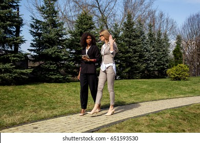 Two serious attractive businesswomen walking and having conversation. One womam is black.