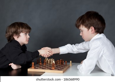 Two serious boy playing chess, studio, gray background