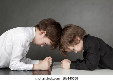 Two serious boys looking at each other, struggle, contrast, portrait on gray background