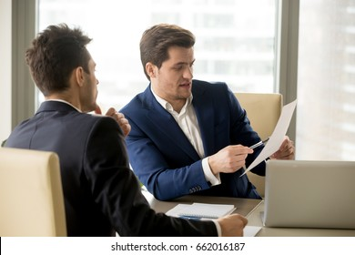 Two serious business partners discussing financial report, analyzing teamwork results, businessman pointing at document, negotiating about contract terms, senior manager giving instructions to junior