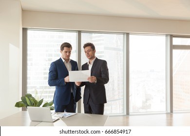 Two serious businessmen discussing building plan, investment adviser offering new project to investor, partners considering construction investment, joint venture business, buying real estate