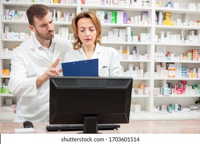 Two serious male and female pharmacist standing behind the counter in a pharmacy, discussing and talking. Healthcare and medicine concept.