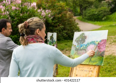 Two serious professional painters standing in front of their easels and painting outdoors with background of beautiful trees