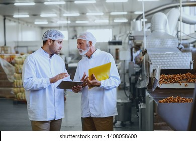 Two serious supervisors in sterile uniforms talking about quality of salty sticks. Older one holding folder with documents while younger one holding tablet. Food plant interior.