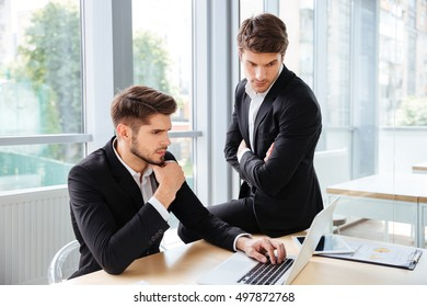 Two serious young businessmen working and using laptop in office together