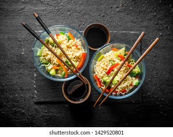 Two servings of instant noodles with broccoli, bell pepper and cucumber. On black rustic background