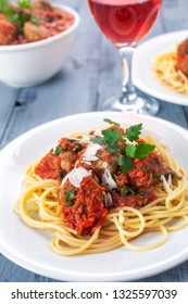 Two servings of meatballs with tomato sauce, spaghetti, parmesan and parsley