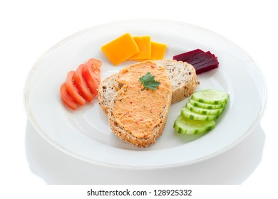 Two Sesame Bread Slices with Hummus Spread, Tomato, Beetroot, Cucumber and Cheese on a White Plate