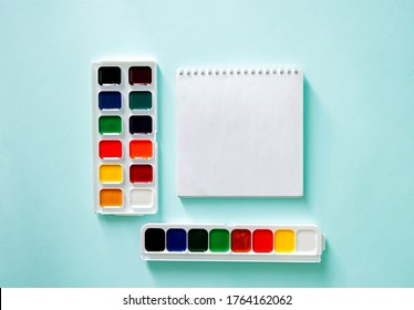 Two sets of color Watercolor paints and white clear sheet of note book on a light blue background. Horizontal photo. Flat lay minimalistic composition. Back to school, college, education concept