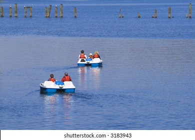 Two sets of daytrippers in pedalos on Loch Lomond, Scotland.