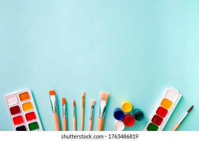 Two sets of multicolored watercolor paints, five gouache paints, three light beige brushes with orange pile and wooden texture, three brushes with white pile, one brush with brown pile, and five