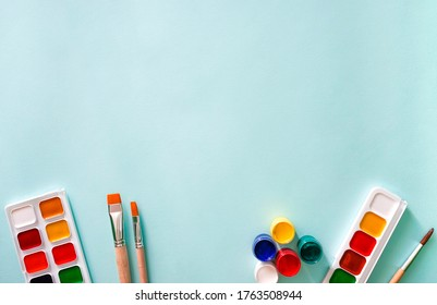 Two sets of multicolored watercolor paints, five gouache paints, two light beige brushes with orange pile and wooden texture and ome brush with brown pile on a light blue background. Horizontal photo