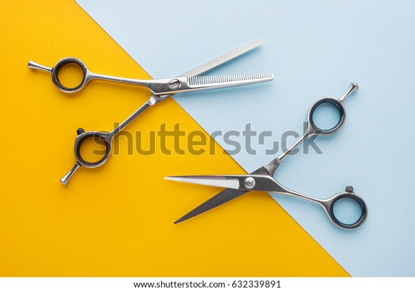 Two sets of stainless steel hairdressing scissors arranged horizontally and parallel to one another
