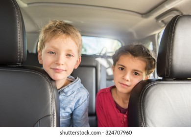 Two seven years old are sitting at the back of a car They are looking at camera,  stretching to reach the front seats The blond boy is wearing a blue shirt and the girl a pink top