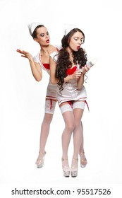 two sexy beautiful surprised female brunette doctors in red lingerie white stocking and red lips on a white background long curly hair with medicine equipment full length
