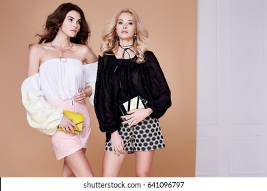 Two sexy blonde and brunette woman friend or rival beautiful face wear silk blouse short skirt casual clothes accessory and jewelry fashion model style makeup studio handbag summer collection.