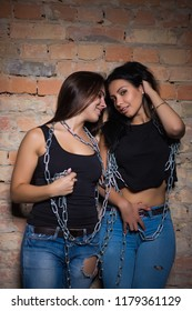 Two sexy brunettes in black t-shirts and jeans posing with chains near the wall