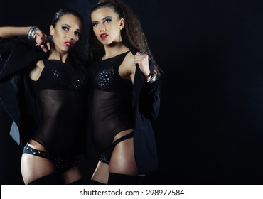 Two sexy dancing woman in black lingerie, night club.