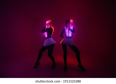 Two sexy disco dancers move in UV costumes. Parties and dances.