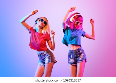 Two sexy fashionable DJ girl dance. Colorful neon uv mixed light. Rave house music vibes. Slim woman with Dyed Hair, makeup. High Fashion. Night Club neon dancing concept.