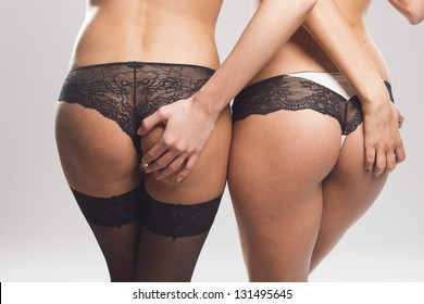 Two sexy female asses in lingerie on gray isolated