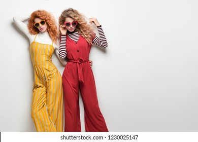Two Sexy Girl in Trendy Glamor Outfit with Curly Hairstyle. Fashion. Gorgeous Woman in Red Yellow jumpsuit, Sunglasses, heels posing in Studio. Young Playful Sisters Friends. Vintage Style