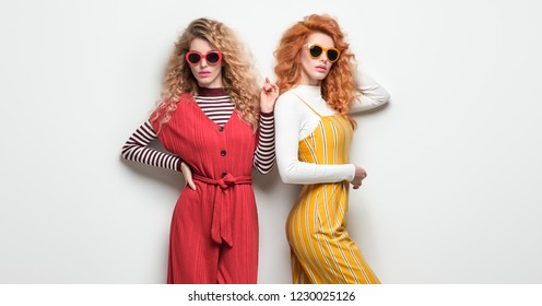 Two Sexy Girl in Trendy Outfit with Curly Hairstyle. Fashion. Gorgeous Woman in Red Yellow jumpsuit, Sunglasses posing in Studio. Young Playful Sisters Friends. Vintage Creative Style