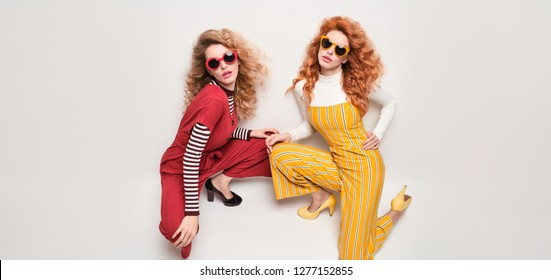 Two Sexy Girl in Trendy Outfit with Curly Hairstyle, makeup. Fashionable Gorgeous Woman in Red Yellow jumpsuit, heels posing in Studio. Young Playful Sisters. Vintage fashion Style