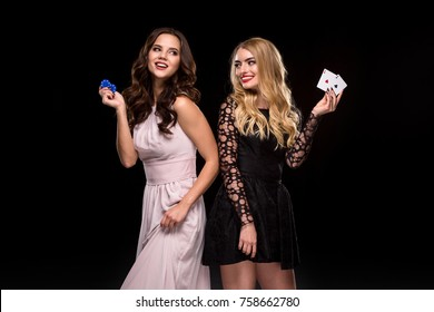Two Sexy girls brunette and blonde, posing with chips in her hands, poker concept black background