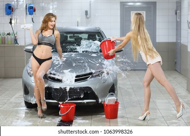 Two sexy girls cheerfully wash the car in a car wash room