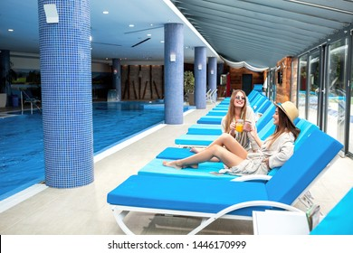 Two sexy girls having fun while relaxing on adjustable beach chairs