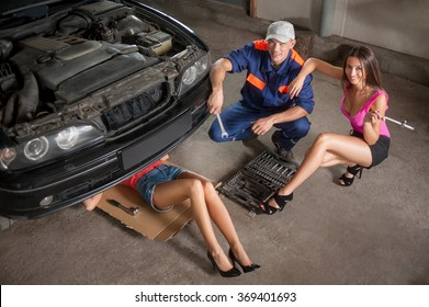 Two sexy girls in high heels and a man in uniform fixing car at auto repair shop. Girl is lying under the car with open hood