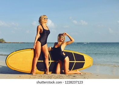 Two sexy girls posing near surfboard on the beach