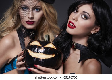 Two sexy Halloween girls with pumpkin
