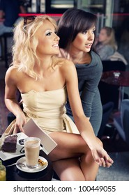 Two sexy ladies in a cafe