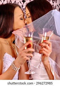 Two sexy lesbian women with champagne on wallpaper background.