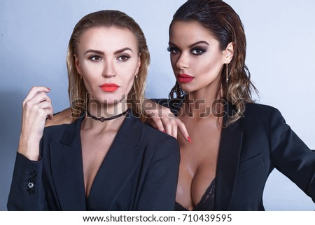 Two sexy models with perfect body, strong make up and red lips looking at  the