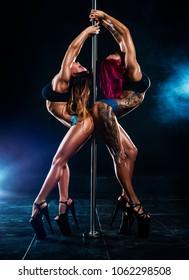 Two sexy pole dancing women team in dark interior with smoke. Tattoo on body.