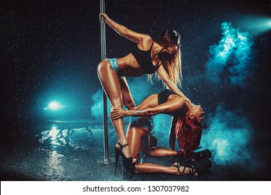 Two sexy pole dancing women team in dark interior with smoke and water. Tattoo on hand.