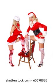 Two sexy woman in red costume put foot on the red chair