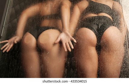 Two sexy Woman's buttocks behind old dirty glass in water studio. Water drops on ass.