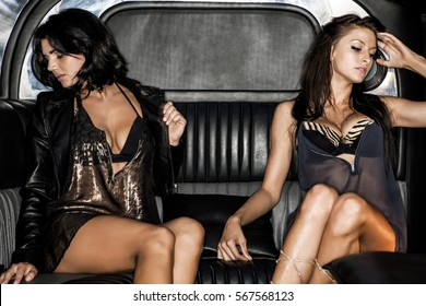 Two sexy women in provocative clothing sitting in a high class vehicle  and giving a hot and sexy pose with their see through dresses, shiny black hair and pretty places looking away.