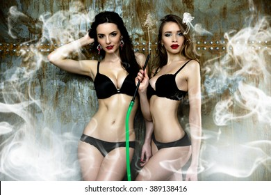 Two sexy young women in black underwear smoking hookah with weathered metal wall on background