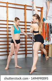 Two sexy young women pole dancers assisting each other during practice on pylon