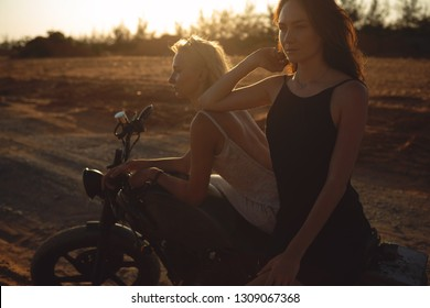 Two sexy young women sit on motorcycle at sunset. Traveling and active