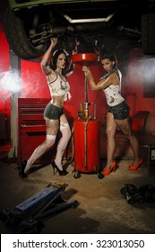 Two sexy young women working under a vehicle and let the used oil